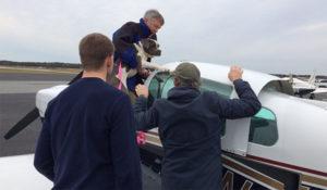 Pilots loading rescue dog into a Grumman aircraft.